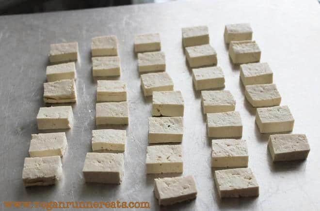 Arranging tofu on a cookie sheet for baking in the oven.