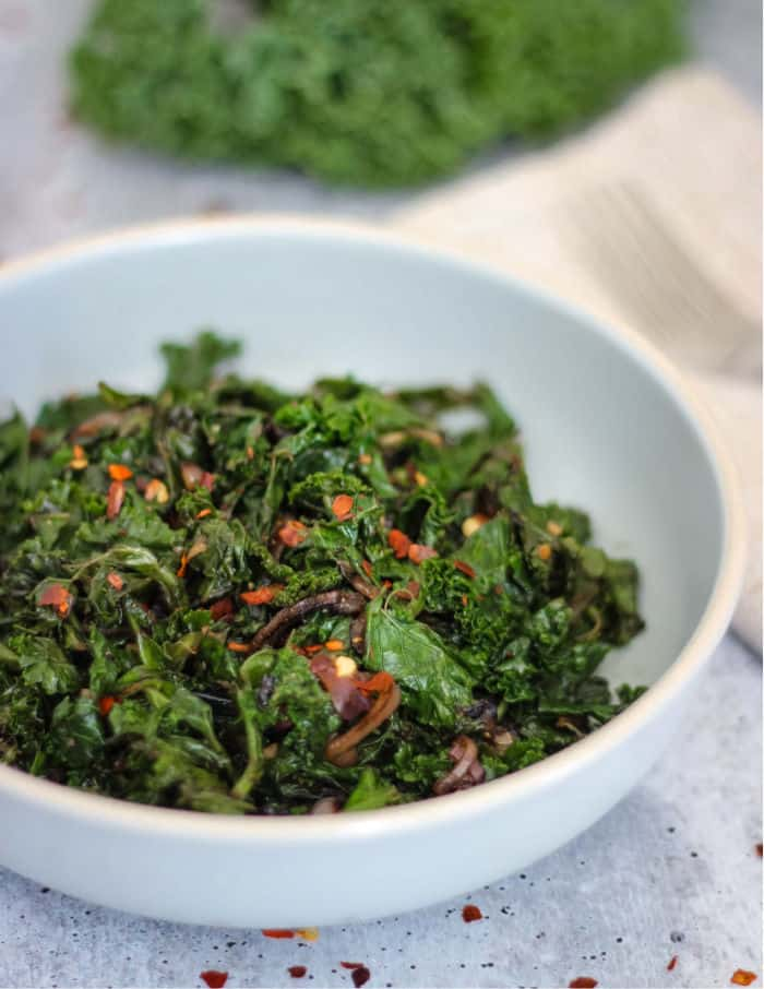 Cooked balsamic sauteed kale and onions in a light blue bowl with a fresh kale leaf in the background